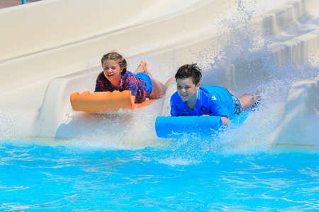 e 27: Rhodes,Greece-Jun 27,2016:Two young children on the mat racer slide in Water park,Mat racer slide is very popular for young people in the Water Park.Water Water Park is located in Faliraki on the island of Rhodes in Greece and one of the most largest in E Editorial