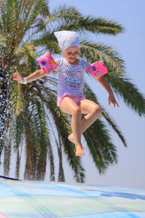 litle: Rhodes,Greece-August 8,2016:Cute litle girl with the scarf on the vet bubble.Vet bubble is very popular for young people in the Water Park.Water Water Park is located on the island of Rhodes in Greece and one of the most largest in Europe and is a very po Editorial
