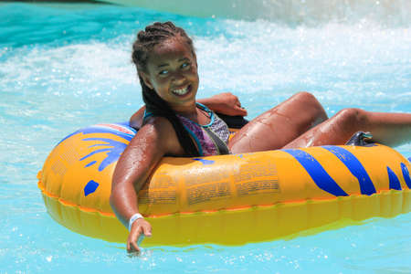 Rhodes, Greece-augus t 13,2016:The girl after rafting slide in the  Water park.Rafting slide is one of many popular game for adults and children in park.Water Water Park is located on the island of Rhodes in Greece and one of the most largest in Europe an