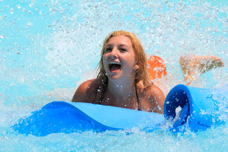Rhodes,Greece-July 30,2016:The girl joying after  mat racer slide.Mat racer slide is very popular for young people in the Water Park.Water Water Park is located in Faliraki on the island of Rhodes in Greece and one of the most largest in Europe and is a v Editorial