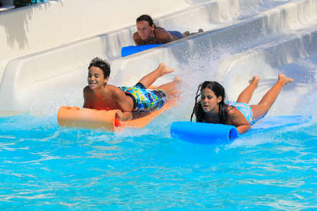 brethren: Rhodes,Greece-July 30,2016:Familly on the mat racer slide.Mat racer slide is very popular for young people in the Water Park.Water Water Park is located on the island of Rhodes in Greece and one of the most largest in Europe and is a very popular place fo