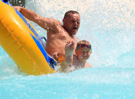 exhilaration: Rhodes, Greece-July 30,2016:father and son on the rafting slide in the  Water park.Rafting slide is one of many popular game for adults and children in park.Water Water Park is located in Faliraki on the island of Rhodes in Greece and one of the most larg