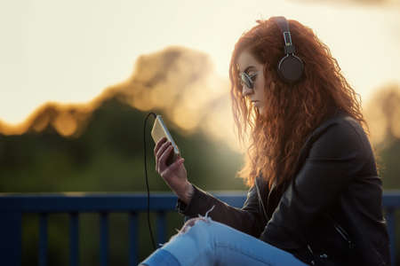 lady on phone: Red-haired girl with listening to music on a bridge at sunset