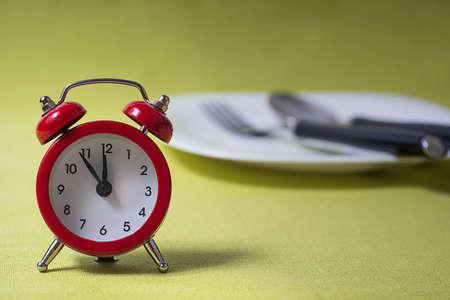 Time to eat concept,  clock on plate Stock Photo
