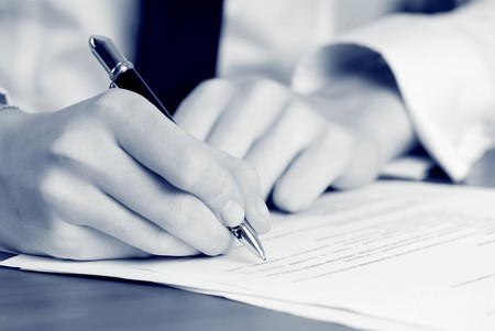 business law: persons hand signing an important document Stock Photo