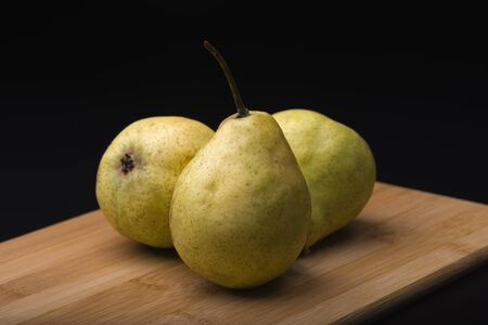 Green pears on a wooden table. Pears close-up. Juicy pears.