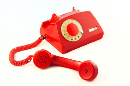 Old red plastic phone on a white background.