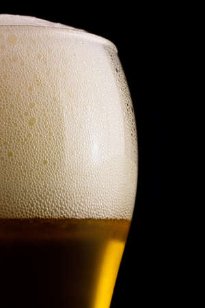Part of a glass of cold beer is a light froth. Stock Photo