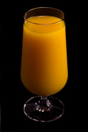 Glass of orange juice isolated on black.