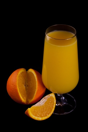 Glass of orange juice and orange slice isolated on black. Stock Photo