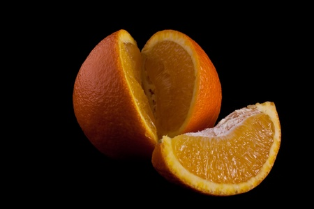 cut orange isolated on black background.