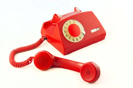Old red plastic phone on a white background. photo