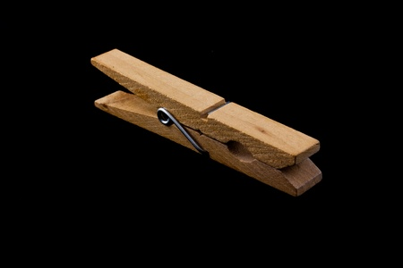 clothes peg: Wooden clothes peg isolated on a black background.