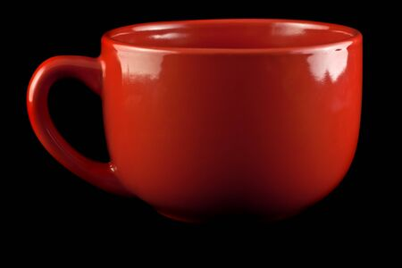 Red porcelain cup on a black background.