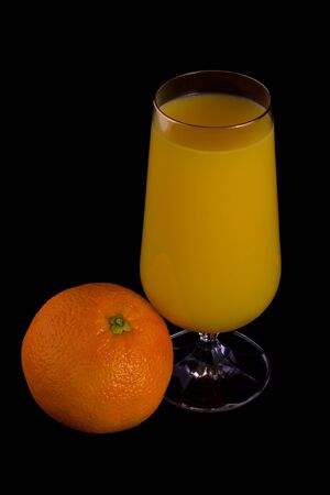 Glass of orange juice and orange isolated on black. Stock Photo