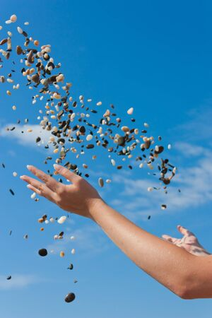 Toss a handful of stones with his hands in the sky. Фото со стока