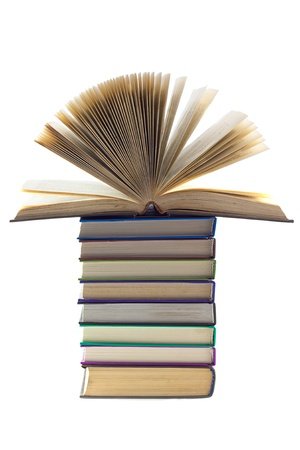 A stack of books on top of all an open book isolated on white background.