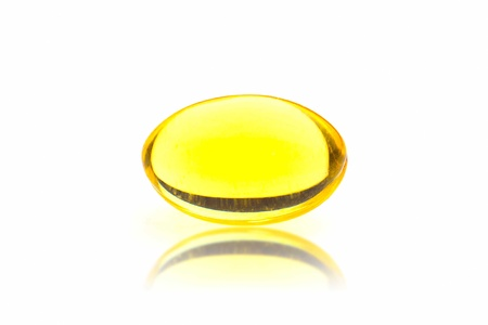 One yellow pills isolated on white background.