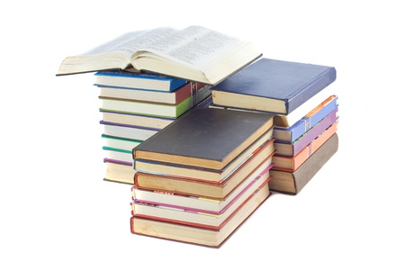 A stack of books on top of all an open book isolated on white background