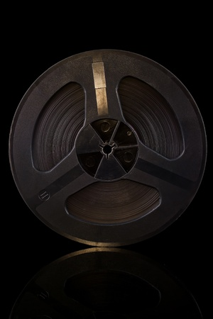 The old reel tape isolated on a black background  Фото со стока