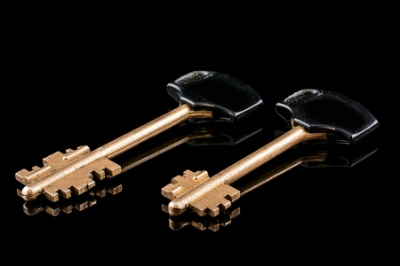 Two golden metal key, isolated on a black background  Stock Photo