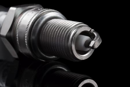 One spark plug on a black background