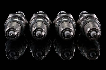 Four spark plugs on a black background Stock Photo - 14015211