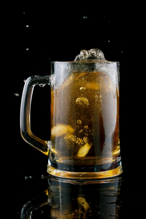 threw: In a cold beer, threw a piece of ice on a black background