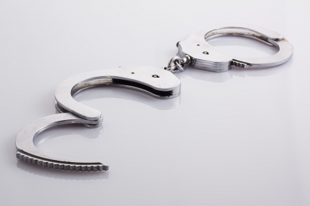 Handcuffs are on a white background   Фото со стока