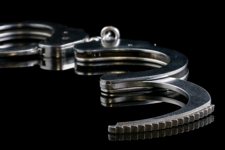 Handcuffs are on a black background  The small depth of field   Stock Photo - 14919773