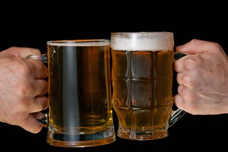 Two male hands holding a glass of beer on a black background