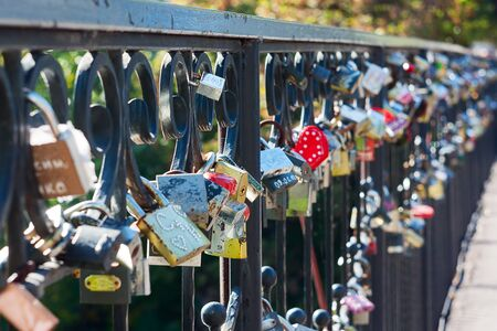 Many different locks hung on a bridge  These locks newlyweds hang a sign of eternal love
