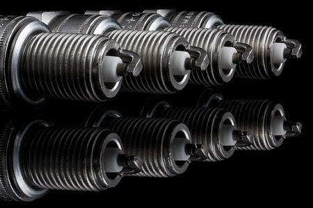 Four spark plugs on a black background  Stock Photo - 15531426