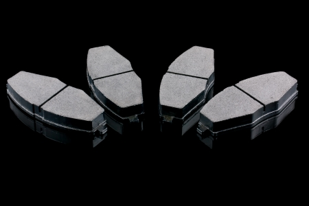 A set of four new automobile brake pads on a black background