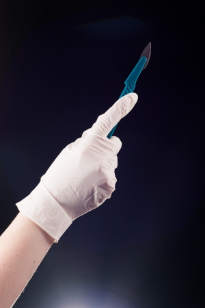 Medical scalpel in his hand, which is a rubber glove