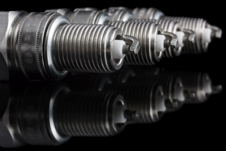 Four spark plugs on a black background