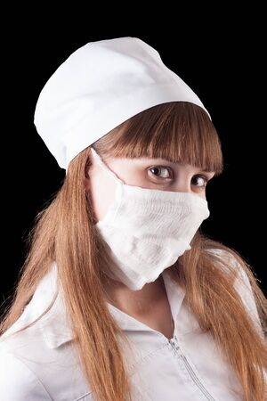 Nurse in uniform and mask on a black background  Stock Photo - 16622504