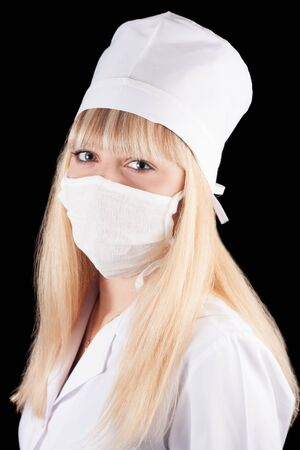 Nurse in uniform and mask on a black background  Stock Photo - 16622126
