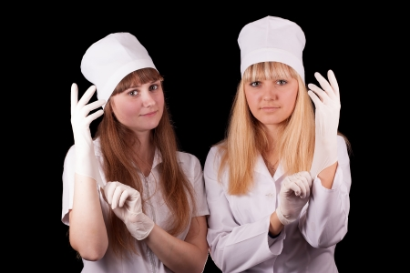 Two nurses wear protective gloves on a black background Stock Photo - 16622234