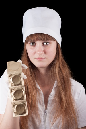 Nurse in uniform hold condoms on a black background  Stock Photo - 16622463