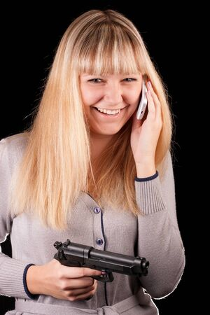 A young girl on a black background with a gun  Stock Photo - 16622608