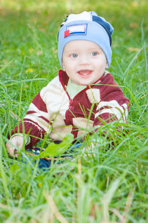 A little boy sitting on the green grass in the park grass, smiling  Stock Photo - 16758027