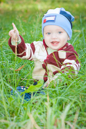 A little boy sitting on the green grass in the park grass, smiling  photo