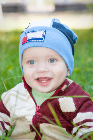 A little boy sitting on the green grass in the park grass, smiling  Stock Photo - 16758086