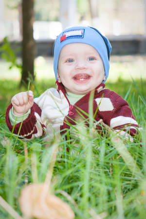 A little boy sitting on the green grass in the park grass, smiling Stock Photo - 16758047