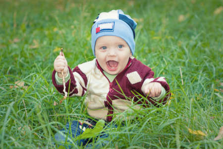 A little boy sitting on the green grass in the park grass, smiling Stock Photo - 16758078