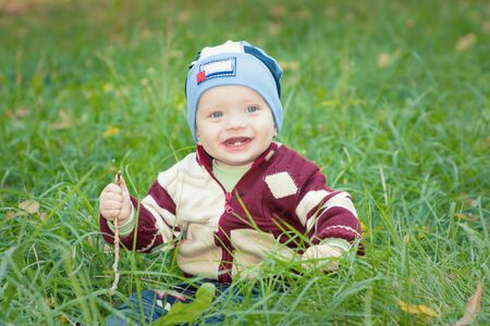 A little boy sitting on the green grass in the park grass, smiling Stock Photo - 16758082