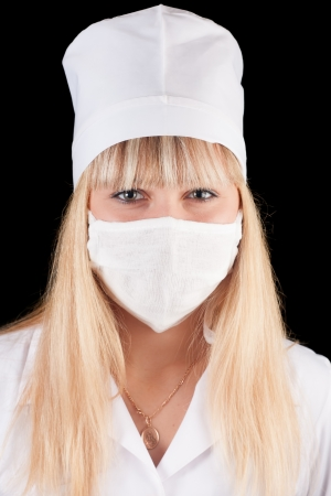 Nurse in uniform and mask on a black background  Stock Photo - 16757886