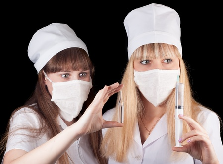 Two nurses in uniform on a black background  Stock Photo - 16748302