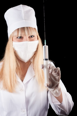 Nurse hold syringe in hand on a black background Stock Photo - 16757888